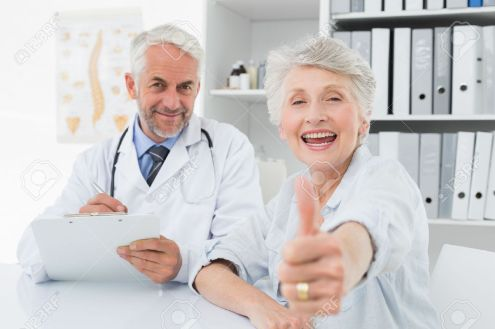 27206409-Portrait-of-a-happy-senior-patient-gesturing-thumbs-up-with-doctor-at-the-medical-office-Stock-Photo